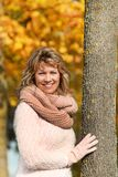 Happy mature woman leaning against a tree in front of autumn lea stock photos