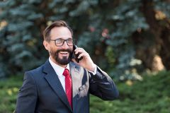 Portrait of attractive happy professional businessman dressed in suit and glasses talking on mobile phone in green park. stock image