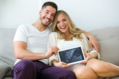 Attractive happy young man and pregnant smiling woman looking at camera while holding digital tablet at home. Portrait of attractive happy young men and stock photos