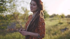 Portrait of an attractive hippie woman with dreadlocks in the woods at sunset having good time outdoors