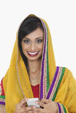 Portrait of an attractive Indian female in traditional wear holding cell phone over white background Royalty Free Stock Photography