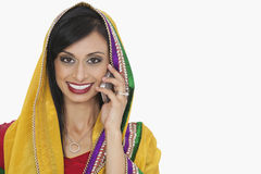 Portrait of an attractive Indian woman in traditional wear answering phone call over white background Stock Photography