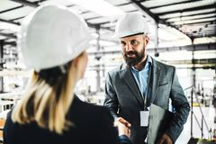 A portrait of an industrial man and woman engineer in a factory, shaking hands. Royalty Free Stock Photo