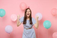 Portrait of attractive joyful young woman in birthday hat blue dress doing winner gesture screming on pink background stock photo