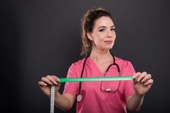 Portrait of attractive lady doctor holding measuring tape Stock Photo