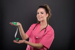 Portrait of attractive lady doctor holding measuring tape Royalty Free Stock Photography