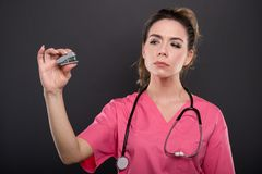 Portrait of attractive lady doctor holding small stapler Stock Image