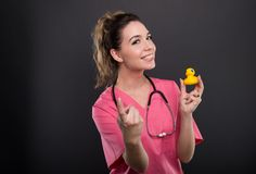 Portrait of attractive lady doctor inviting for a bath. Holding a duck on black background with copypsace advertising area Stock Images