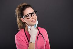 Portrait of attractive lady doctor wearing glasses and mask. On black background with copypsace advertising area Stock Photography