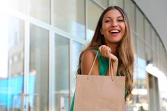 Portrait of attractive laughing woman with shopper bag in her hand with flare. Beauty fashion smiling girl doing shopping. Let`s go shopping concept. Copy Stock Photos