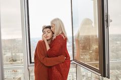 Portrait of attractive lesbian couple in love wearing red clothes, hugging near opened window while standing on balcony Stock Photo