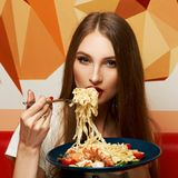 Attractive woman eating seafood pasta royalty free stock photo