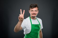Portrait of attractive male supermarket employer showing peace g. Esture on black background Royalty Free Stock Image