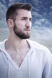 Portrait of an attractive man with beard. In front of a blue sky with some clouds Stock Photo