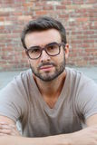 Portrait of attractive man on red brick wall background / Closeup of young interesting natural male Stock Photography