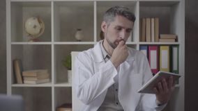 Portrait attractive man in white robe looking in the camera showing tablet with picture of x-ray of lungs. Skillful stock video