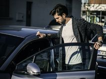 Handsome man next to car in white shirt. Portrait of attractive man in white shirt entering his new stylish polished car outdoor in city street Royalty Free Stock Image