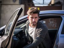 Handsome man next to car in white shirt. Portrait of attractive man in white shirt getting out of his new stylish polished car outdoor in city street Royalty Free Stock Photo