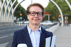 Portrait of attractive mature businesswoman commuter smiling in busy city, holding a coffee cup and paperwork folder Royalty Free Stock Photography