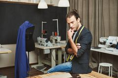 Portrait of attractive mature concentrated fashion designer sitting in his workshop, looking aside, holding chin with royalty free stock images