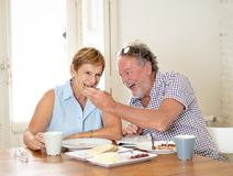 Portrait of a beautiful senior couple having breakfast together. Portrait of a attractive mature retired couple having breakfast together at home enjoying the Stock Image