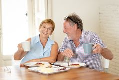 Portrait of a beautiful senior couple having breakfast together. Portrait of a attractive mature retired couple having breakfast together at home enjoying the Stock Photography