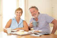 Portrait of a beautiful senior couple having breakfast together. Portrait of a attractive mature retired couple having breakfast together at home enjoying the Royalty Free Stock Photography