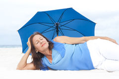 Relaxed Mature woman lying at beach Stock Photo