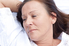 Sad contemplating mature woman resting in bed. Portrait attractive mature woman resting in bed with sad and contemplating expression Royalty Free Stock Image