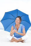 Attractive Mature woman blue umbrella beach Royalty Free Stock Photo