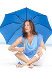 Worried Mature woman blue umbrella beach Stock Photos