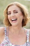 Portrait of an attractive mature woman smiling outdoors Stock Image