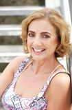 Portrait of an attractive middle aged woman smiling outdoors Royalty Free Stock Images