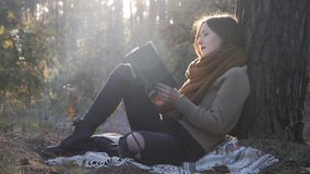 Portrait of attractive model woman in cozy clothes and boots sitting in fall forest, reading book and enjoying autumn sunny day.  stock footage