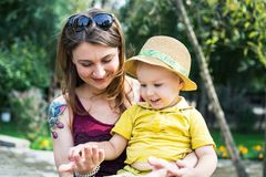 Portrait of an attractive mother with her baby 2 years old, smiling and looking at her palms, walking in a park in the summer royalty free stock images
