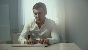 Portrait of attractive office worker typing on wireless keyboard in slow motion stock footage