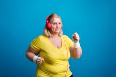 Portrait of an attractive overweight woman in studio on a blue background, jogging. Portrait of an attractive blond overweight woman with hedphones in studio on stock photo