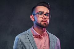 Portrait of attractive pensive man in checkered blazer, pink shirt and glasses stock images