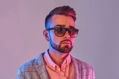 Portrait of attractive pensive man in checkeret blazer and sunglasses stock images