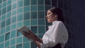 Portrait of attractive pleased business woman standing against business center background and working on her tablet. Portrait of attractive pleased business stock video footage