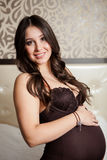 Portrait of an attractive pregnant woman touching her belly while sitting on a bed at home royalty free stock photos