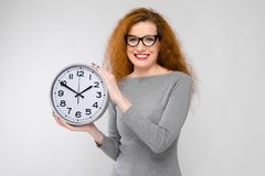 Young woman with clocks. Portrait of attractive red-haired woman in glasses and dress isolated on grey background holding big clock being late concept Stock Images