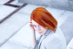 Portrait of attractive redhead business woman with smile sitting outside on the stairs Stock Photography