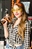 Portrait of the attractive salesgirl with long blonde hair and yellow glasses in home improvement store with a drill Stock Image