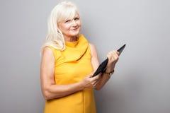 Portrait of attractive senior businesswoman using tablet. Stock Photos
