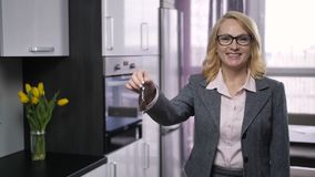 Attractive senior realtor offering keys to camera. Portrait of attractive senior female realtor standing near the kitchen in new apartment for sale, and offering stock video