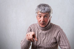 A portrait of attractive senior man with gray hair and wrinkles having surprised expression pointing at you with his index finger Royalty Free Stock Image