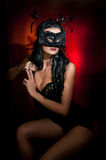 Portrait of attractive sensual young woman with mask, indoors. Sensual brunette lady posing provocatively on red background Stock Photography