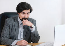 Portrait of attractive serious businessman working at his desk i Royalty Free Stock Images
