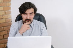 Portrait of attractive serious businessman working at the office Stock Photography